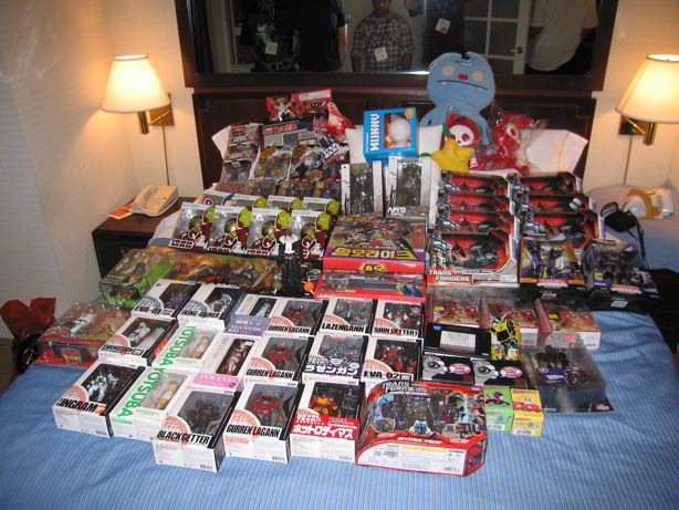 tons of sdcc exclusive toys on the bed