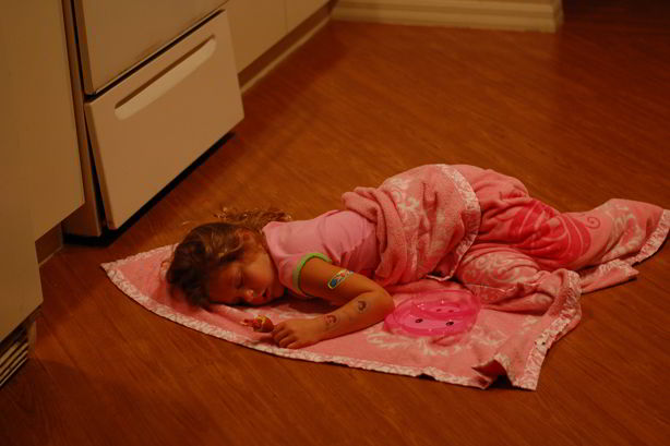 kid sleeping on a wood floor