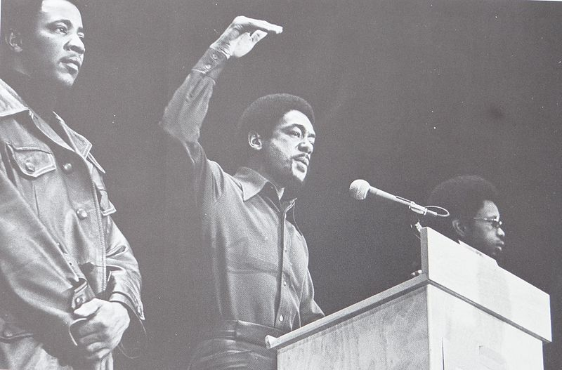bobby seale speaking at the podium flanked by 2 black panthers