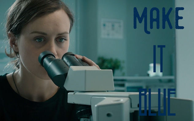 abi looking through a microscope in a scene with a blue tint