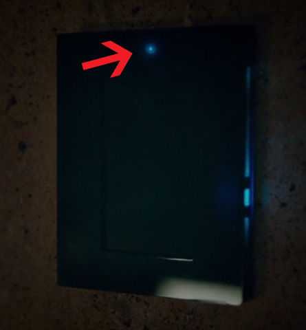 blue led light indicating hidden camera on a panel in a scene from the titan
