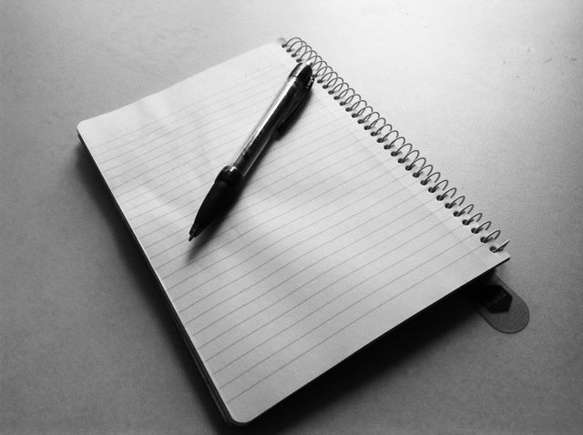 notepad with a pen on top